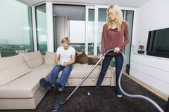 Woman vacuuming while man play video game in living room at home Royalty Free Stock Image