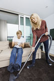 Woman vacuuming while man play video game in living room at home Stock Photos