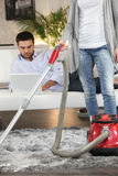 Woman vacuuming rug. In front of lazy boyfriend Stock Photography