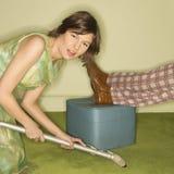 Woman vacuuming rug. Royalty Free Stock Image