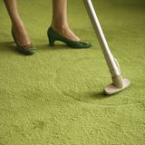 Woman vacuuming rug. Close-up of Caucasian female feet with vacuum extension against green retro carpet royalty free stock photos