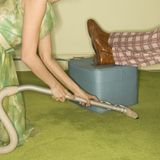 Woman vacuuming rug. Royalty Free Stock Image