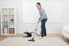 Woman vacuuming rug at home Royalty Free Stock Photos