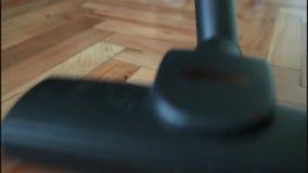 Woman vacuuming wooden floor stock footage