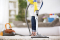 Woman vacuums carpet Stock Image