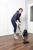 Woman vacuums the flat Stock Photo