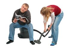 Woman vacuums, man sits Stock Photos