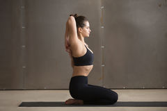 Woman in Vajrasana pose with hands hooked behind the back Royalty Free Stock Photo