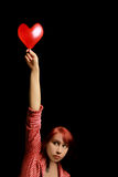 Woman with valentine heart. Pretty woman with red valentine heart on a black background Royalty Free Stock Photo