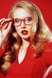 Woman vamp. Beautiful young woman with magnificent blonde hair wearing red dress and elegant red glasses. Beauty, fashion. Optics, eyewear. Red background Royalty Free Stock Image