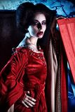 Woman vampire. Bloodthirsty female vampire standing near the coffin on the night cemetery Stock Image