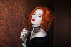 Charming girl with red hair. A woman is a vampire with pale skin and red hair in a black dress and a necklace on her neck. Girl witch with vampire claws and red royalty free stock photography