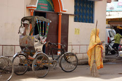 Woman in Varanasi, India. Woman in traditional sari with broom standing on street with man sitting in bicycle rickshaw in front of building in holy city of Royalty Free Stock Photo