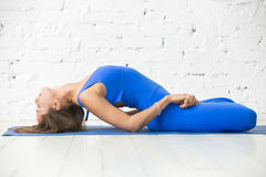 Woman in variation of Matsyasana pose, lotus legs, white studio Royalty Free Stock Photography