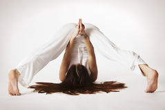 Woman in variation of plough Yoga posture Stock Image