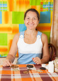 Woman with various seeds. Mature woman with various seeds on table royalty free stock photography