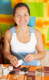 Woman with various seeds. Mature woman with various seeds at home royalty free stock image