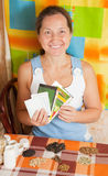 Woman with various seeds. Mature woman with various seeds at home royalty free stock images