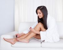 Woman varnishing her toenails Royalty Free Stock Images