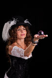 Woman in vaudeville costume with glass marble. A woman in vaudeville costume is seen peering at a glass marble in her hand, magician-style Royalty Free Stock Photos