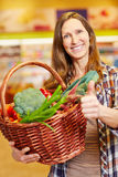 Woman with vegetable basket holding thumbs up Royalty Free Stock Image