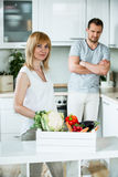 Woman with vegetable box in kitchen, man looking sceptical Stock Image