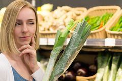 A Woman with Vegetables Thinks in the Store royalty free stock images