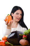 Woman with vegetables. Young woman with fresh vegetables in front of her giving you a orange capsicum,check also stock photos