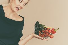 Woman with vegetables, negative face expression. Adult woman do not like to eat vegetables, healthy food, vegetarian products. Female holding small shopping Stock Photo