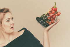 Woman with vegetables, negative face expression Royalty Free Stock Images