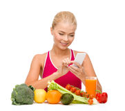 Woman with vegetables pointing at smartphone. Dieting, food, healthcare and technology concept - smiling sporty woman with fruits and vegetables counting Royalty Free Stock Image