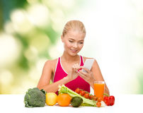 Woman with vegetables pointing at smartphone. Dieting, food, healthcare and technology concept - smiling sporty woman with fruits and vegetables counting Stock Images
