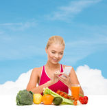 Woman with vegetables pointing at smartphone. Dieting, food, healthcare and technology concept - smiling sporty woman with fruits and vegetables counting Royalty Free Stock Photos