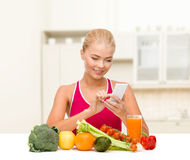 Woman with vegetables pointing at smartphone. Dieting, food, healthcare and technology concept - smiling sporty woman with fruits and vegetables counting Royalty Free Stock Images