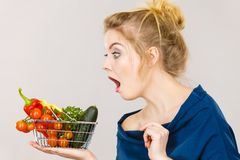 Woman with vegetables, shocked face expression. Adult woman do not like to eat raw food, questioning healthy lifestyle recommendations, origin vegetagles. Female stock images