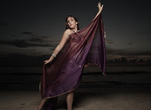 Woman with a veil on the beach. Beautiful woman dancing with a veil on the beach during sunrise Stock Photography