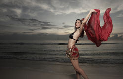 Woman with a veil on the beach. Beautiful woman dancing with a veil on the beach during sunrise Royalty Free Stock Image