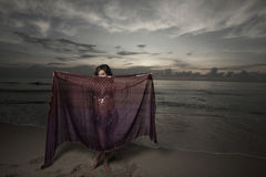 Woman with a veil on the beach Stock Image