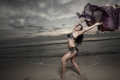 Woman with a veil on the beach. Beautiful woman dancing with a veil on the beach during sunrise Stock Photo