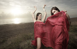 Woman with a veil dancing on the beach. Beautiful young belly dancers dancing on the beach Stock Image