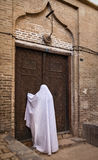 Woman in Veil Knocking on the Old Wooden Door of a Building in Yazd of Iran Royalty Free Stock Photos