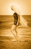 Woman with veil on peaceful sunny beach Royalty Free Stock Photo