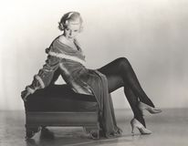 Woman in velvet dress sitting on footstool Royalty Free Stock Images