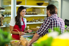 Woman vendor interacting with the man in the grocery store. Smiling woman vendor interacting with the man in the grocery store Stock Photography