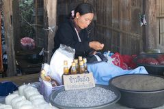 Woman vendor selling rice and sewing at a roadside hill tribe market, Chiang Rai province, Thailand. Chiang Rai, Thailand - December 10th 2014: Woman vendor royalty free stock images