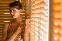 Woman and venetian blind Stock Photo