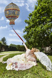 Woman in Venetian costume lying on the green park holding an old balloon