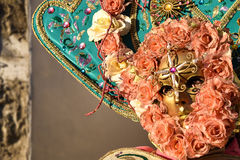Woman with Venetian mask decorated with gold leaf and green cloth, stone background Stock Photo