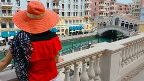 Woman in Venice Doha. Woman on balcony looking at famous bridge reflecting on waters of canals in Venice Doha city. Caucasian tourist at Qanat Quartier in the stock video