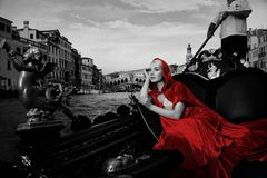 Woman in Venice on gondola. Beautifiul woman in red cloak riding on gondola stock images